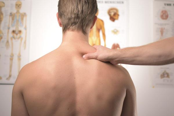 treating upper back pain with massage on man sitting up